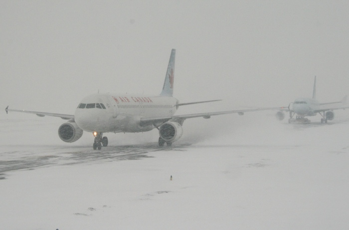 Air Canada planes in snow image by Flickr user Anirudh Koul - Tips for Traveling in the Winter Months