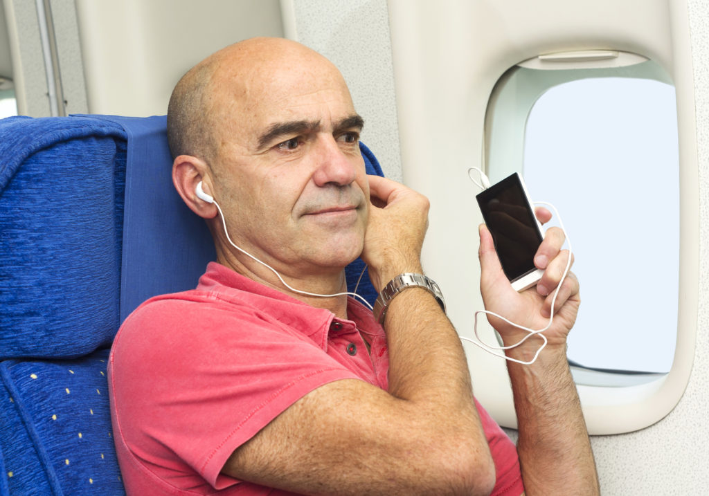 caucasian man passenger in airplane using mobile smart device with headphones