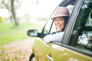 Woman in car looking through the window and wearing hat